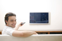 Man sitting on the couch holding a television remote control
