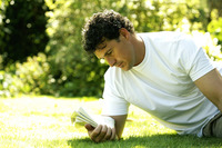 Man sitting on the field reading newspaper