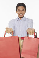 Man smiling and carrying shopping bags