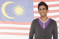 Man standing in front of a malaysian flag