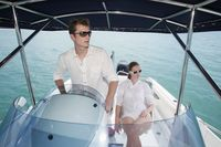 Man steering speedboat, woman sitting beside him