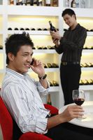 Man talking on the phone, another man is choosing wine in the background