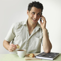 Man talking on the phone while having breakfast