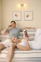 Man talking on the phone while woman is lying down on his lap writing in diary