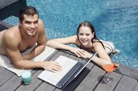 Man using laptop by the pool side, woman in the pool