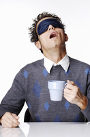 Man with eye mask holding a cup of coffee