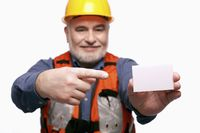 Man with hardhat pointing at a business card