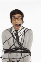 Man with headset wrapped in a tangled cable