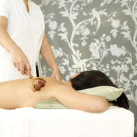 Massage therapist using a wooden massager on woman's back