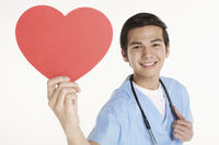Medical personnel holding a cut out heart shape