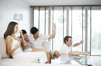 Men and women cheering while watching television at home