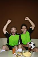 Men cheering while watching football match