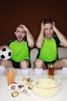 Men touching their heads with disappointment while watching football match
