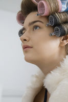 Model in hair curlers wearing fur coat