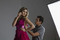 Model on cell phone while designer adjusts dress