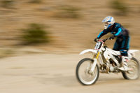 Motocross racer travelling at speed outdoors