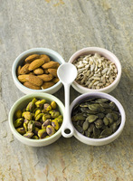 Nut and seed selection in four bowls with white spoon