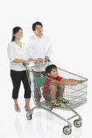 Parents pushing a shopping cart with son in tow