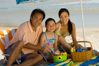 Parents with daughter (7-9) having picnic on beach (portrait)