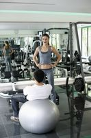 Personal trainer helping man exercising in gymnasium