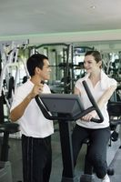 Personal trainer helping woman exercising in gymnasium