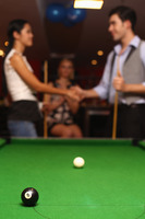 Pool balls on pool table, man and woman shaking hands after the game