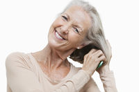 Portrait of smiling senior woman combing her hair against white background