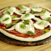 Raw pizza base with basil and mozzarella topping
