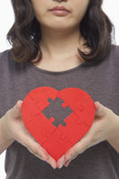 Sad woman holding up a red heart shape with a missing puzzle piece