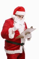 Santa claus holding pen and clipboard