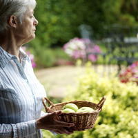 Senior lady holding a basket of fruits