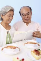 Senior man and woman reading book while enjoying cake and tea