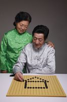 Senior man arranging black pebbles into a house, senior woman watching him