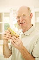 Senior man holding a sandwich