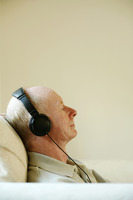 Senior man sitting on the couch listening to music on the headphones