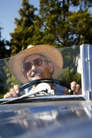 Senior man with hat driving in the car