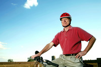 Senior man with helmet posing on bicycle