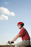 Senior man with safety helmet riding on a bicycle