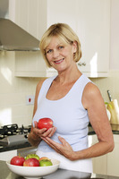 Senior woman holding a red apple while smiling at the camera