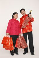 Senior woman holding shopping bags while senior man is showing her a bottle of wine