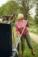 Senior woman playing with her dog while mopping her houseboat