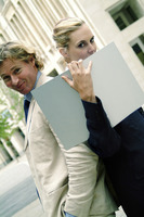 Side shot of a woman holding a file with her back facing the back of a guy