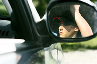 Side view mirror reflection of a boy sitting in a car
