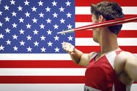Side view of male athlete throwing javelin against american flag