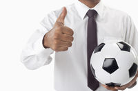 Soccer manager holding a ball and thumbs up