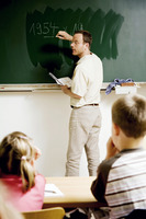 Teacher writing on the blackboard with children paying attention