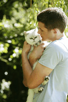 Teenage boy hugging his pet cat