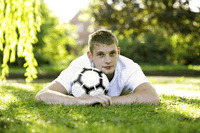 Teenage boy lying forward on the field hugging a soccer ball