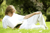Teenage boy lying on the field reading book