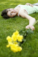 Teenage girl lying down on the field with yellow flowers in her hand